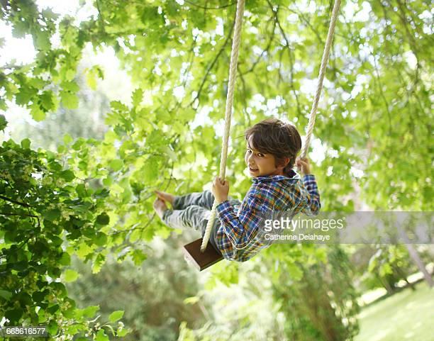 A boy on a swing in the garden