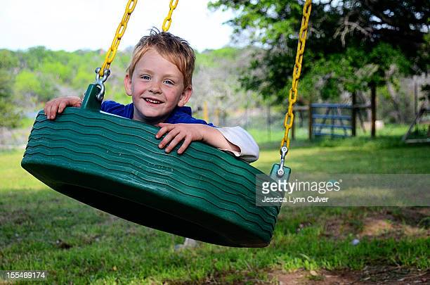 boy on a tire swing in spring - lynn pleasant stock pictures, royalty-free photos & images