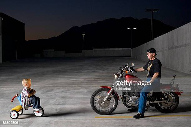 boy on a tricycle next to a man on a motorcycle
