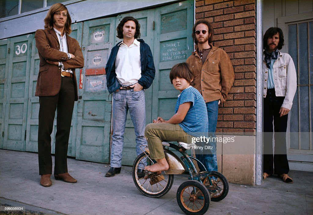 A boy on a tricycle sits among the rock band the Doors who are (left to right): keyboardist Ray Manzarek, singer Jim Morrison, guitarist Robbie Krieger, and drummer John Densmore. The writing between Morrison and Krieger reads: 'I think I know the reason but I can't spell it.'