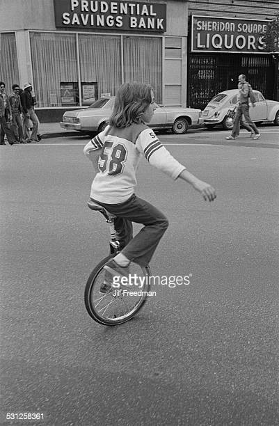A boy on a unicycle in front of a Prudential Savings Bank in Sheridan Square New York City USA circa 1976