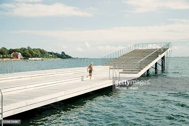 boy on a wooden jetty at harbour bath - funen stock pictures, royalty-free photos & images