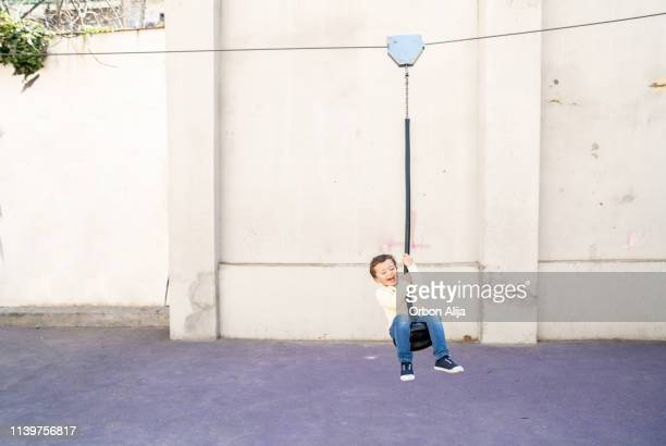 ジップラインの少年 - ファスナー ストックフォトと画像