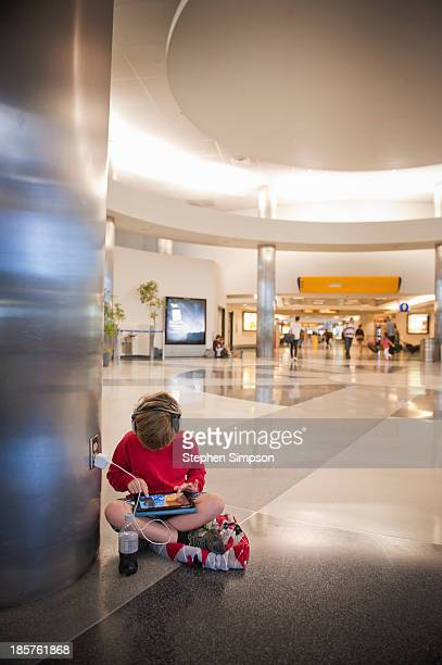 boy on airport floor with tablet computer