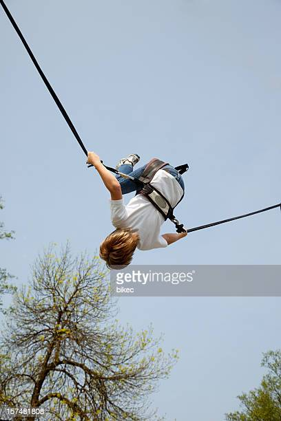 Boy on an elastic rope of a trampoline