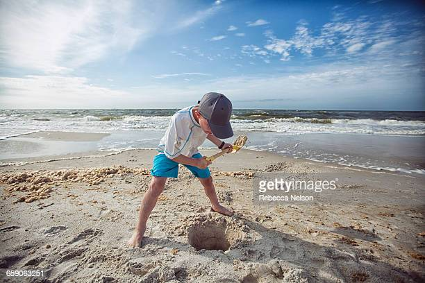 Boy on beach digging hole in sand