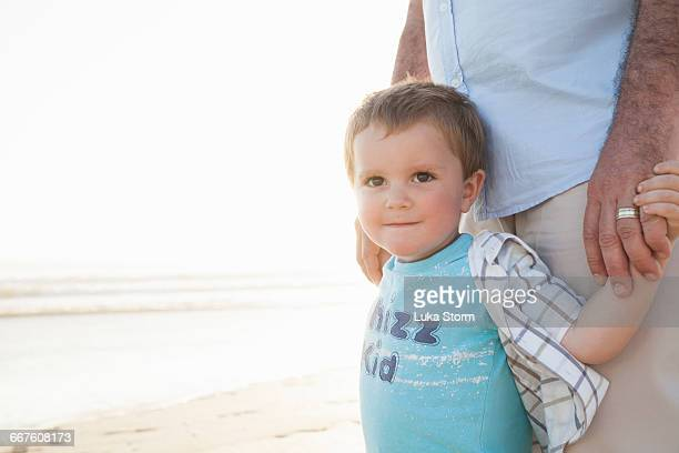 Boy on beach holding fathers hands looking at camera smiling