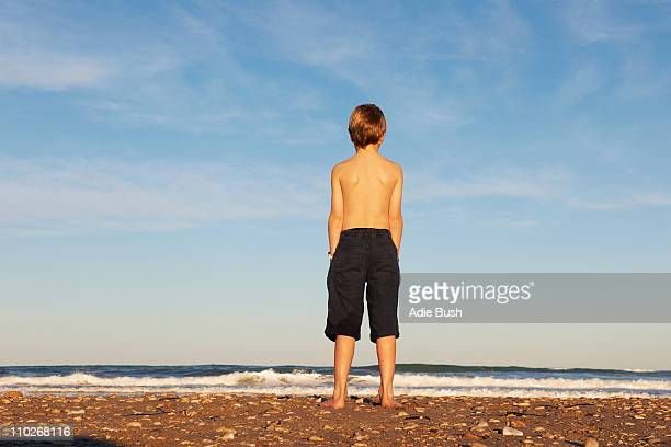 Boy on beach looking out to sea