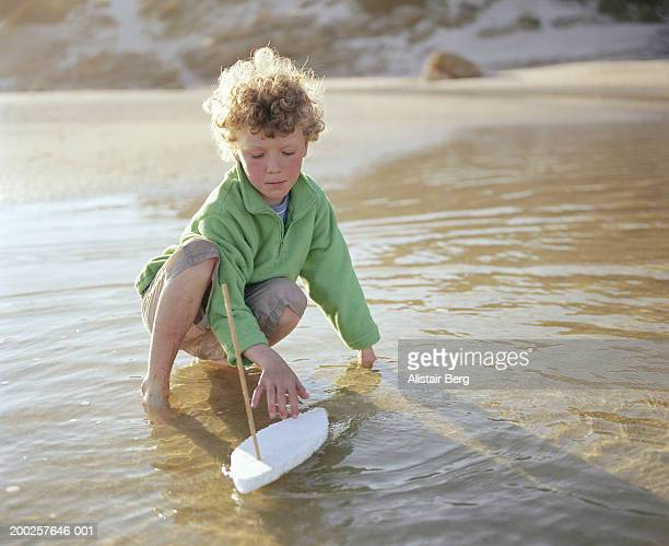 Boy (7-9) on beach playing with makeshift boat