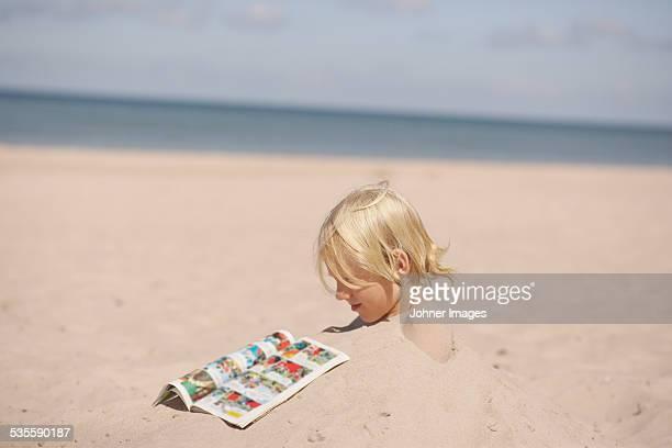 Boy on beach reading comic book
