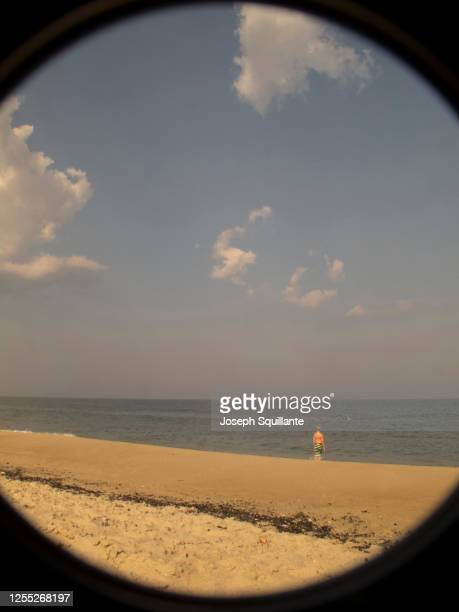 boy on beach through a looking glass - joseph squillante stock pictures, royalty-free photos & images