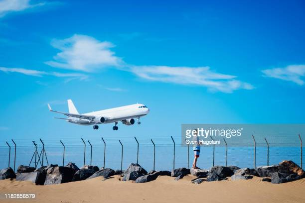 boy on beach watching airplane flying low in blue sky near lanzarote airport, spain - islas canarias fotografías e imágenes de stock