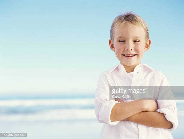 Boy (5-7) on beach with arms crossed, smiling, portrait