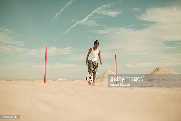 Boy on beach with goalposts and football, doing keepy uppy