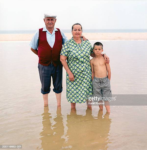 Boy (5-7) on beach with grandparents, portrait