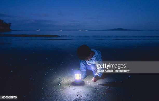 Boy On Beach with Lamp.