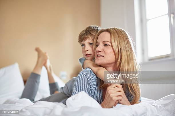 Boy on bed lying on top of mother