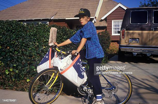 Boy on bicycle delivering newspapers on Route Los Angeles CA