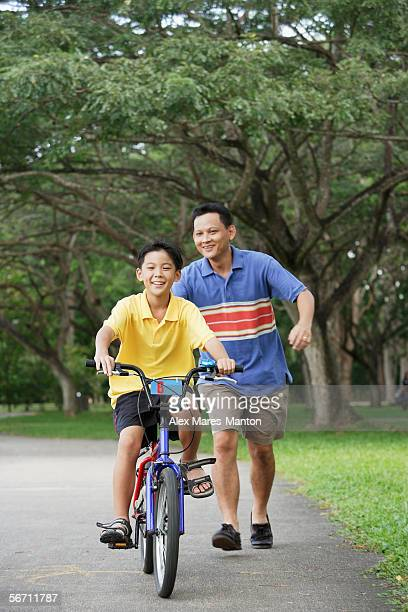 Boy on bicycle, father running behind him, smiling