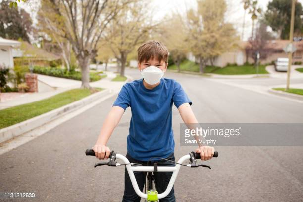 boy on bicycle wearing dust mask - mascherina antipolvere foto e immagini stock