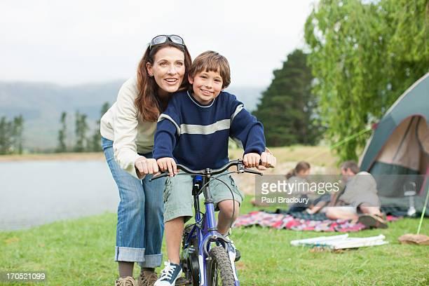 boy on bicycle mientras s'encuentra de viaje de la familia campamento - montar fotografías e imágenes de stock