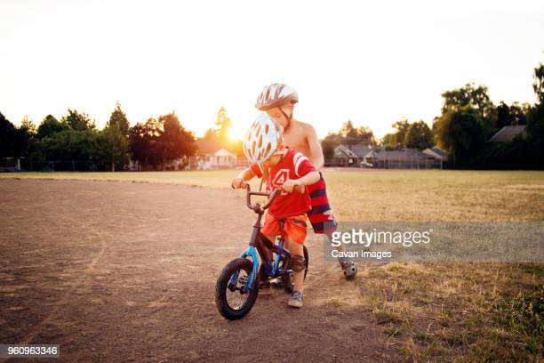Boy on bicycle with brother