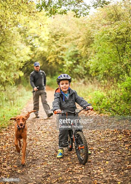 Boy on bike with father and dog
