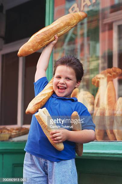 Boy (5-7) on city street with fresh baked loaves of bread