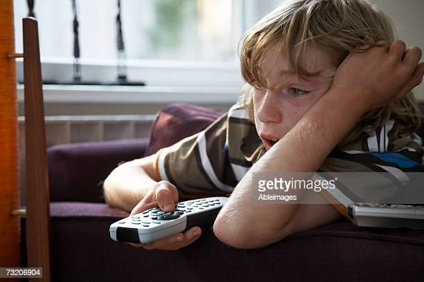 Boy (11-13) on couch, watching television