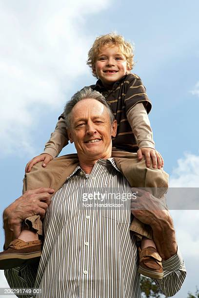 Boy (5-7 years) on grandfather's shoulders outdoors, smiling, portrait