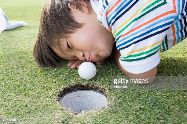 Boy on green blowing golf ball into hole