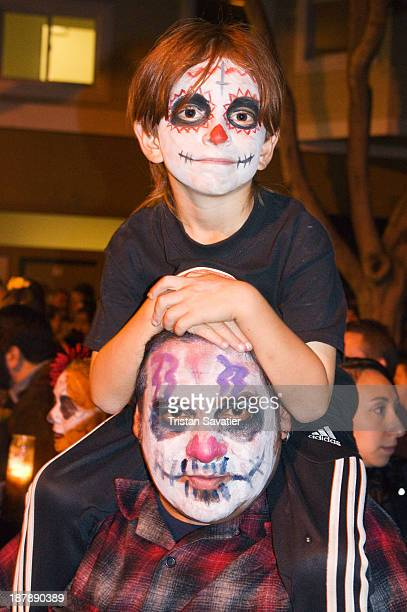 CONTENT] Boy on his father shoulders with Mexicanstyle sugar skull makeup in the annual Dia de los Muertos procession The Day of the Dead is a...