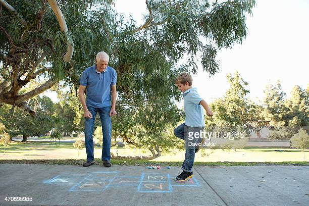 Boy on hopscotch, grandfather watching