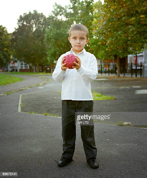 Boy on housing estate holding ball, portrait