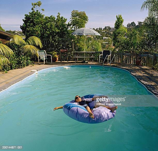 Boy (12-14) on inflatable floating in swimming pool, elevated view