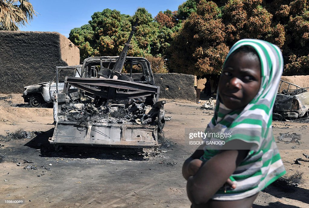 A boy on January 21,2013 in Diabaly stands next to an Islamists pickup truck destroyed during aerial