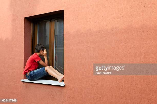 Boy on ledge looking in window