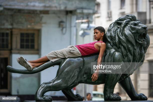 Boy on lion statue Paseo del Museo Havana