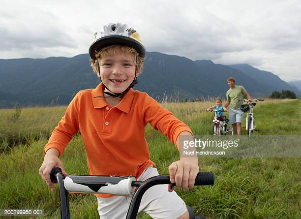 Boy (5-7 years) on mountain bike, smiling, portrait, close-up