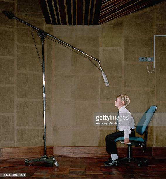 Boy (7-9) on office chair beneath microphone