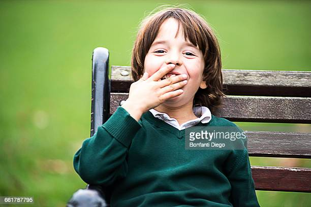 Boy on park bench, hand over mouth looking at camera smiling