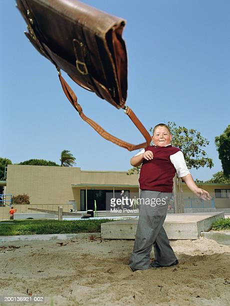 boy (5-7) on playground, throwing satchel like hammer - representar - fotografias e filmes do acervo