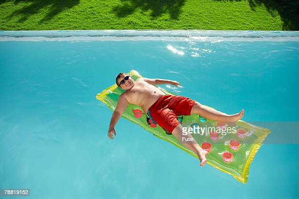 boy on raft in swimming pool - chubby boy stock photos and pictures