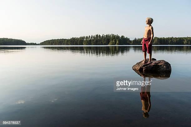 Boy on rock in lake