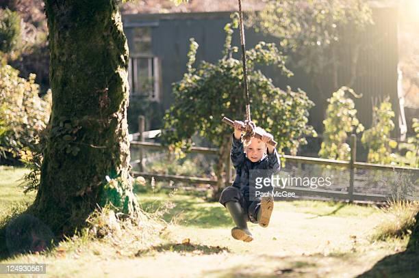 Boy on rope swing in garden