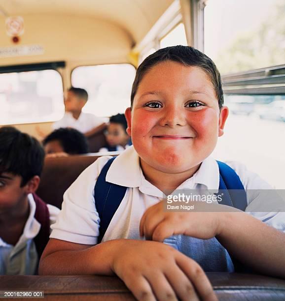 Boy (5-7) on school bus, portrait