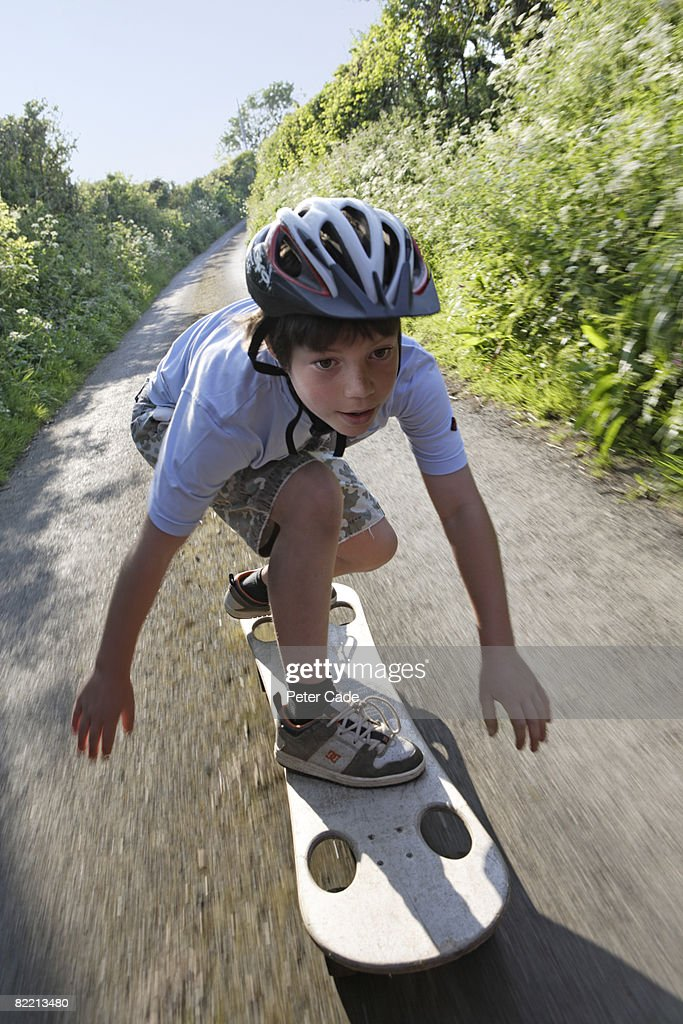 Boy on skateboard in country lane : Stock Photo