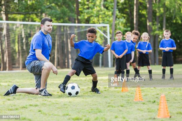 Boy on soccer team practicing, coach watching