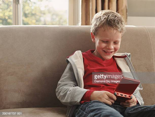 Boy (5-7) on sofa, playing hand held game, smiling