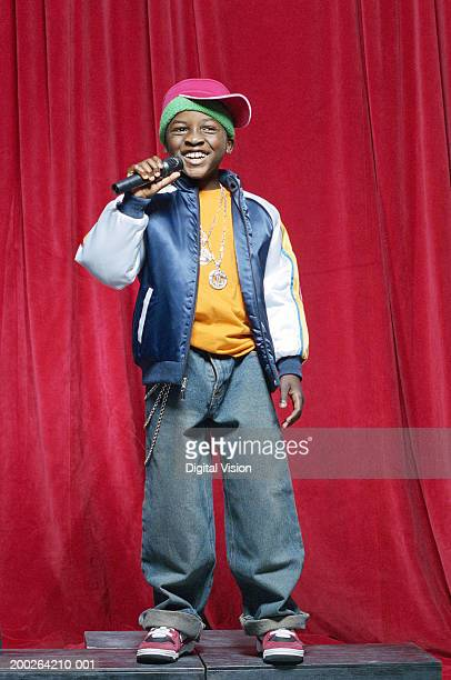 Boy (9-11) on stage holding microphone, smiling